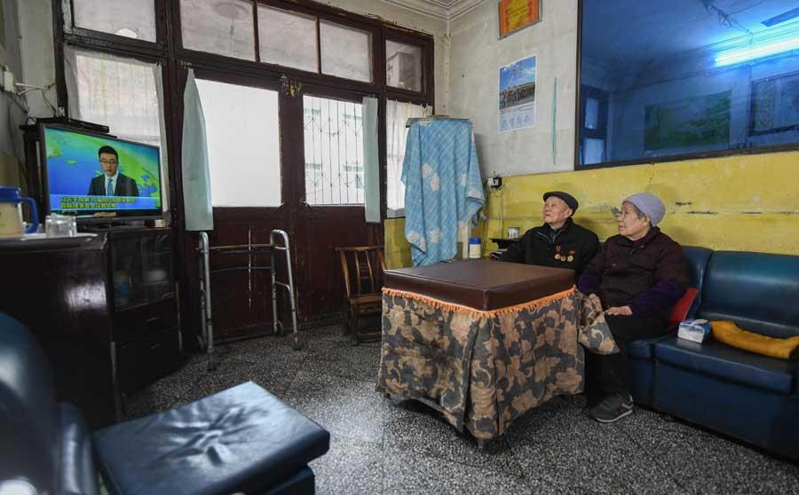 張富清和老伴在住了幾十年的老房子裏看電視