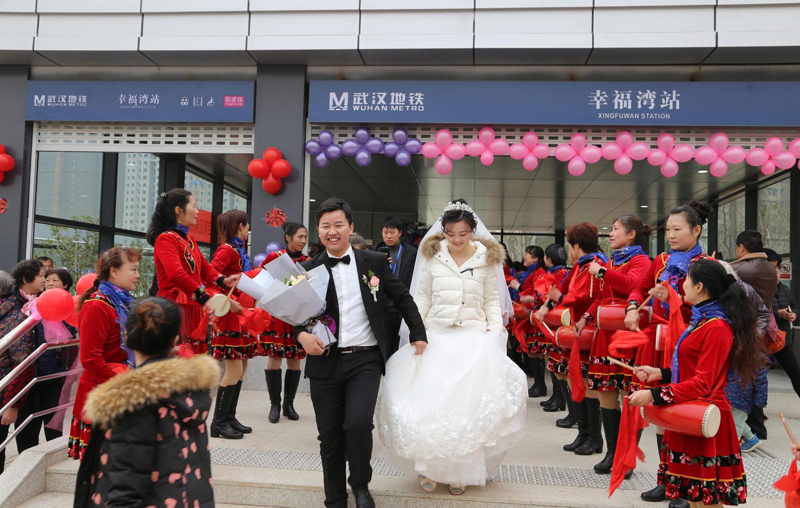 2018年元旦前夕,武汉地铁21号线(阳逻线)后湖大道站站厅举行了一场充满浓郁地铁特色的集体婚礼,21对新人步入婚姻殿堂。图为一对新人走出幸福湾站。(连迅 摄)