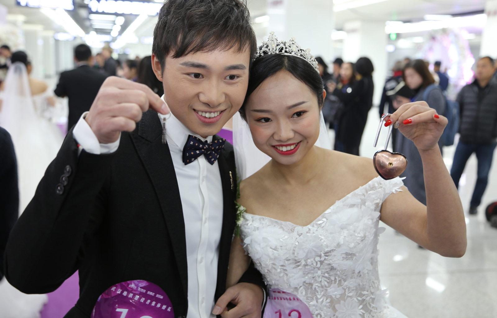 作为地铁承建方的中建三局基础设施公司联合武汉地铁集团,在地铁阳逻线开通之际,为21名地铁建设者举办了别开生面的集体婚礼。图为一对新人展示自己的同心锁。(连迅 摄)