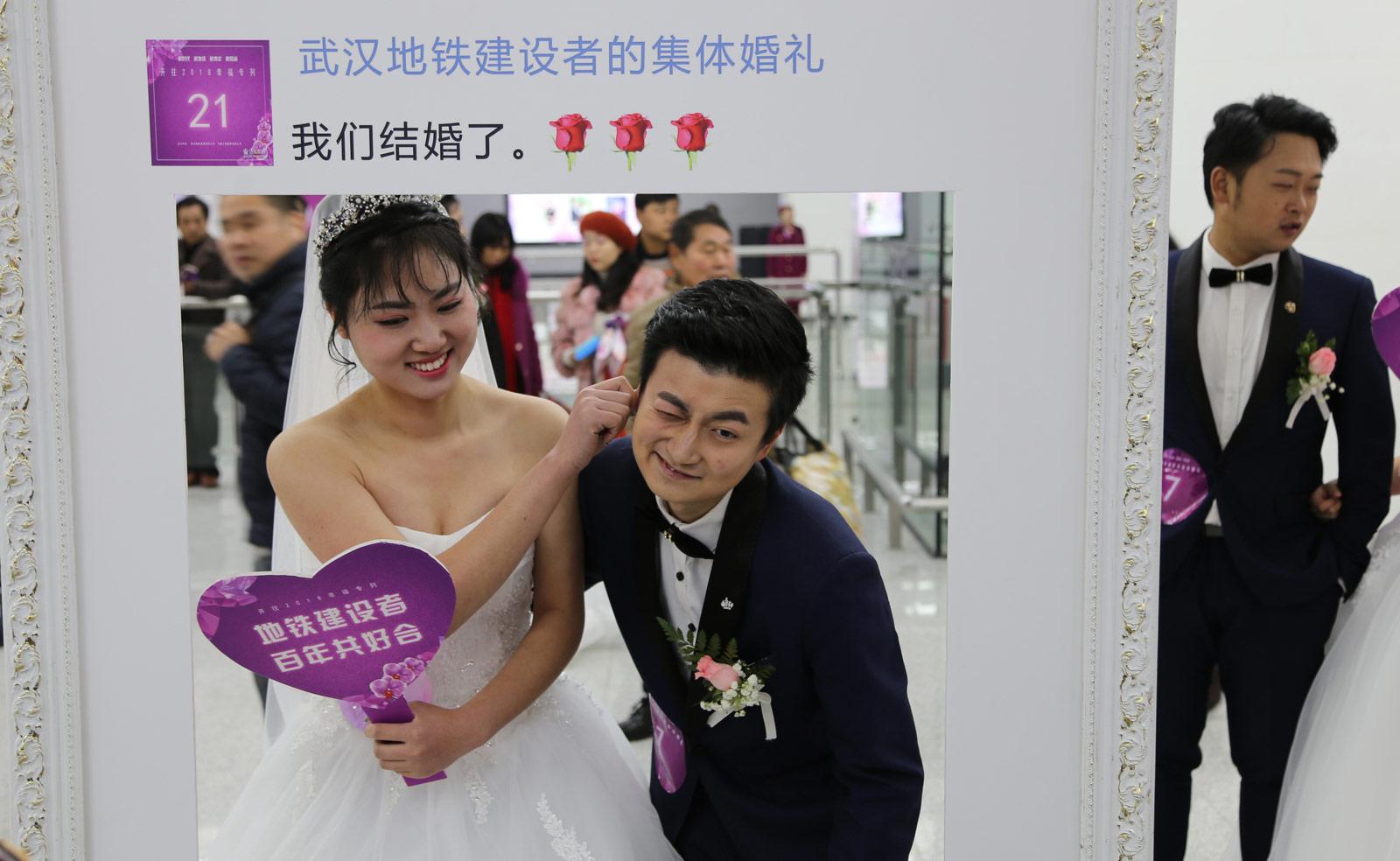 在当天集体婚礼上,新人们做游戏、拍合影、送喜糖,和市民一起分享自己的幸福。图为一对新人拍摄的趣味合影照。(连迅 摄)