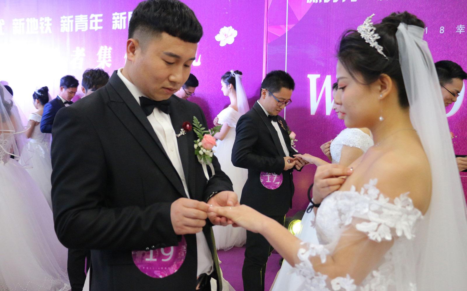 在当天集体婚礼上,新人们做游戏、拍合影、送喜糖,和市民一起分享自己的幸福。图为婚礼上新郎为新娘戴上婚戒。(连迅 摄)