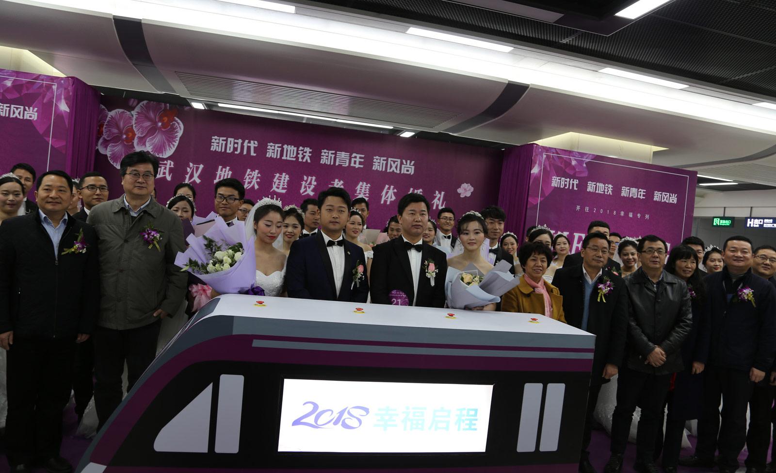 在当天的集体婚礼上,一辆地铁模型缓缓驶来,寓意21对新人将搭乘人生列车幸福启程。(连迅 摄)