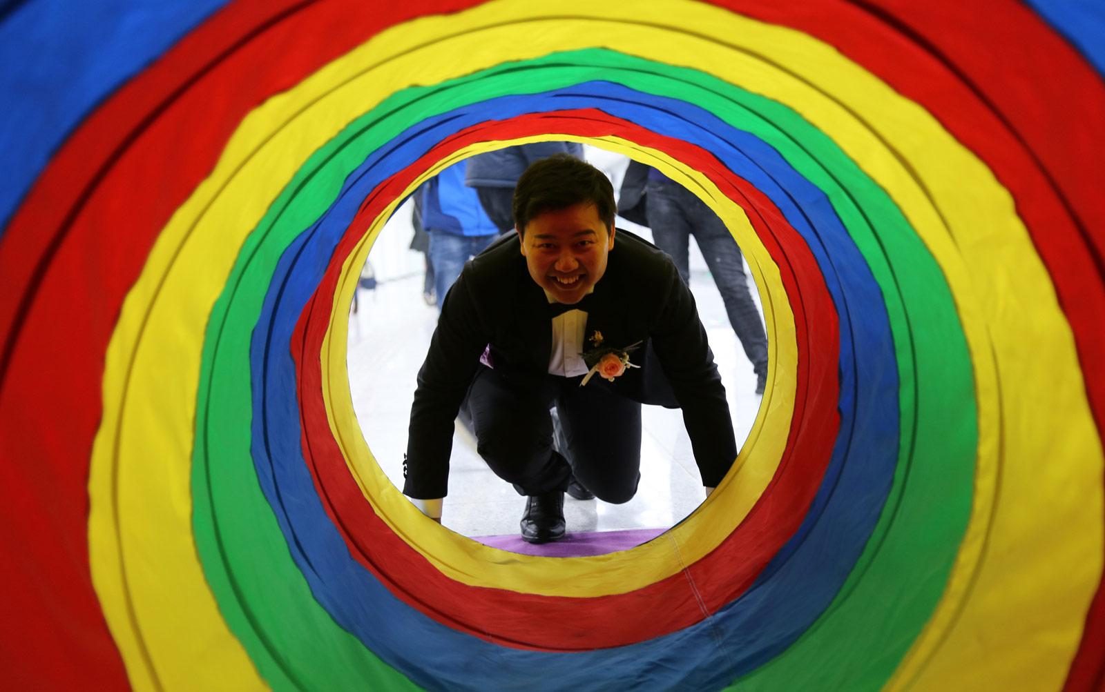 在当天集体婚礼上,新人们做游戏、拍合影、送喜糖,和市民一起分享自己的幸福。图为新郎参加穿越幸福隧道游戏。(连迅 摄)