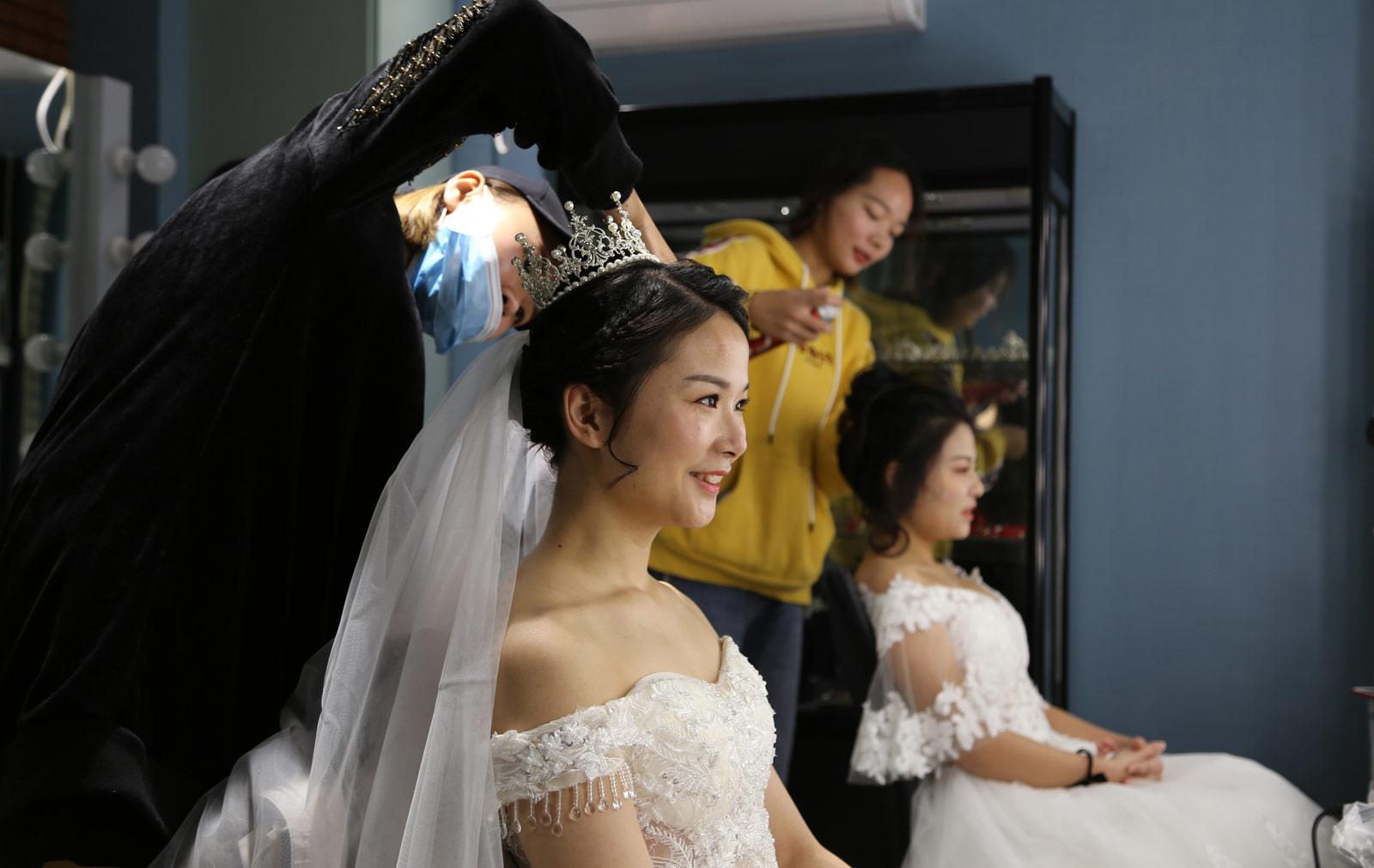 2018年元旦前夕,武汉地铁21号线(阳逻线)后湖大道站站厅举行了一场充满浓郁地铁特色的集体婚礼,21对新人步入婚姻殿堂。图为新娘们化妆参加婚礼。(连迅 摄)