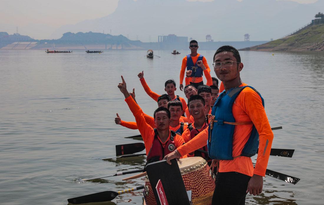 图为参加龙舟比赛的队员为自己加油。新华网发 何宇欣 摄