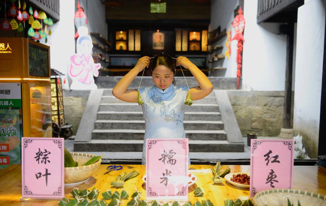 在湖北省秭归县屈原故里景区端午习俗馆居民包不同口味的粽子。新华网 欧阳小洁 摄