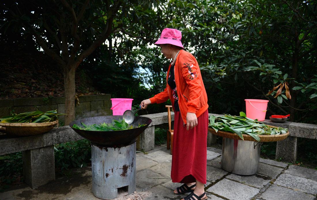 在湖北省秭归县屈原故里景区端午习俗馆居民清洗粽叶。新华网 欧阳小洁 摄