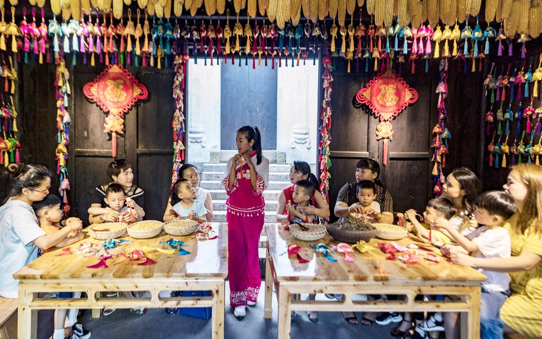 图为在湖北省秭归县屈原故里景区端午习俗馆,家长和孩子学做香包。王爱平 摄