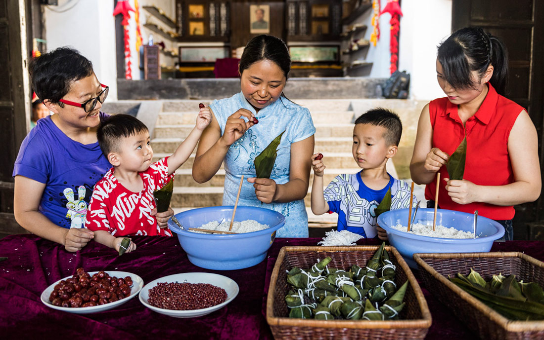 图为在湖北省秭归县屈原故里景区端午习俗馆居民包粽子。