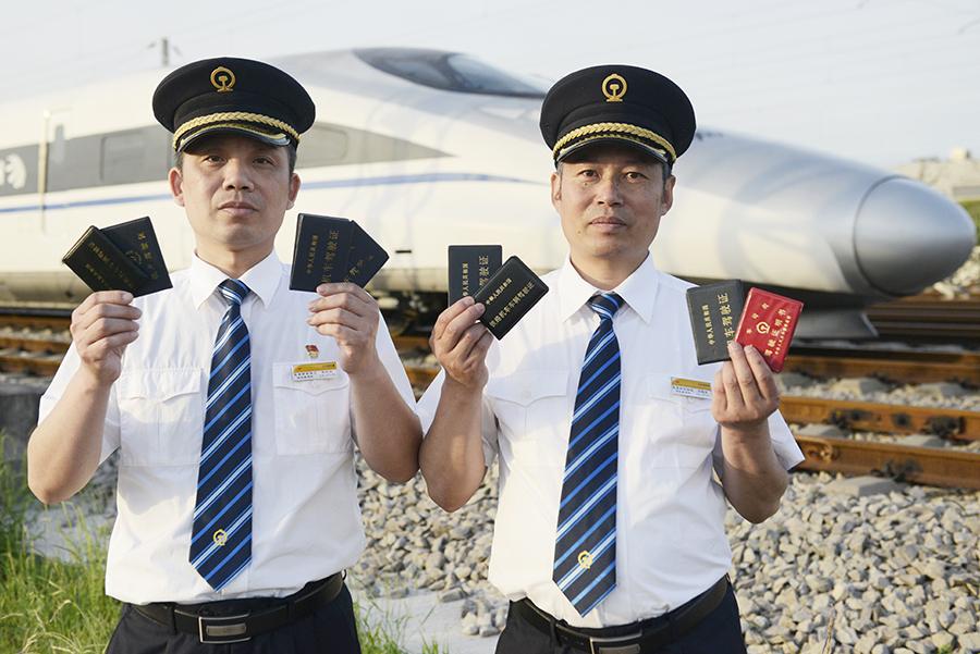 图为刘旭东和陈红生展示他们的四本驾照。新华网发 欧阳小洁摄</br>在近30年的铁路司机生涯中,他们经历了蒸汽机车、内燃机车、电力机车和动车四个阶段。
