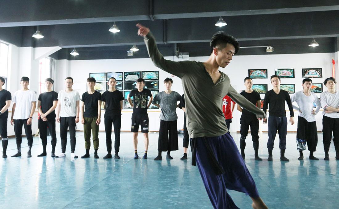 肖雪峰说即便哪一天自己跳不动了,他也不会离开舞蹈。他会去做一名教员,培养更多的年轻人来从事这份事业。图为肖雪峰为年轻演员示范舞蹈动作。(连迅 摄)